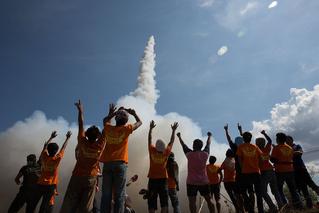 Thai men cheer as their rocket takes off at the Bun Bang Fai Rocket Festival on May 10, 2015 in Yasothon, Thailand. (Photo by Taylor Weidman/Getty Images)