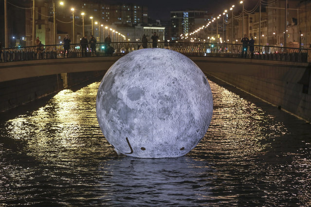 "People look at a giant floating ball depicting the moon's surface, an installation for the ""Festival of Lights"", in the water of Obvodny channel in St. Petersburg, Rusia, Saturday, November 3, 2018. (Photo by Dmitri Lovetsky/AP Photo)"