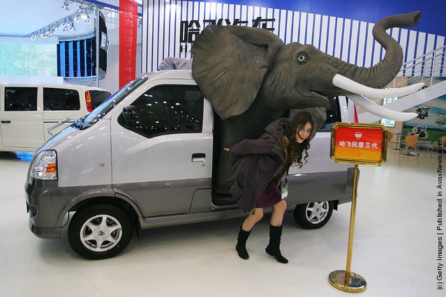 A model poses beside the Hafei J6391 during a special media opening of the Auto China 2008 show