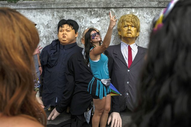 A woman takes a selfie next to giant dolls depicting U.S. President Donald Trump, right, and North Korean leader Kim Jong-un, during carnival celebrations in Olinda, Pernambuco state, Brazil, Monday, March 4, 2019. (Photo by Diego Herculano/AP Photo)