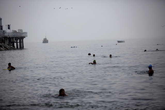 In this April 9, 2015 photo, people swim in the Pacific Ocean off Fishermen's Beach in Lima, Peru. Swimmers arrive at Peru's coast shortly before dawn and wade into the waters of the Pacific Ocean, seeking relief from the ailments their doctors have been unable to cure. (Photo by Rodrigo Abd/AP Photo)