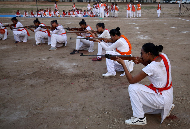 Members of Durga Vahini, the women's wing of Vishva Hindu Parishad (VHP), a Hindu nationalist organisation, show their self-defence skills with firearms at the concluding ceremony of a weeklong women's training camp on the outskirts of Ahmedabad, India on May 25, 2019. (Photo by Amit Dave/Reuters)
