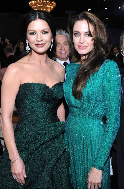 Michael Douglas with gorgeous girls in green. Catherine Zeta-Jones and Angelina Jolie at Golden Globe Awards in 2011. (Photo by Vince Bucci/Getty Images)