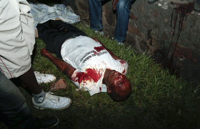 The body of Zedi Feruzi, the leader of  Burundi's opposition party UDP, lays on the ground near his home, in Bujumbura, Burundi, Saturday May 23, 2015. The leader of an opposition party was killed Saturday by unknown assailants in the nation's capital, Bujumbura, local media reported. (Photo by Berthier Mugiraneza/AP Photo)