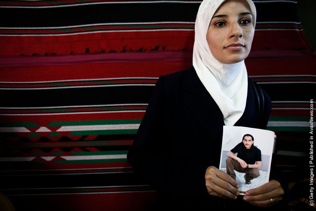 A Palestinian woman holds a picture of a relative jailed in Israel during a protest calling for the release of Palestinian prisoners