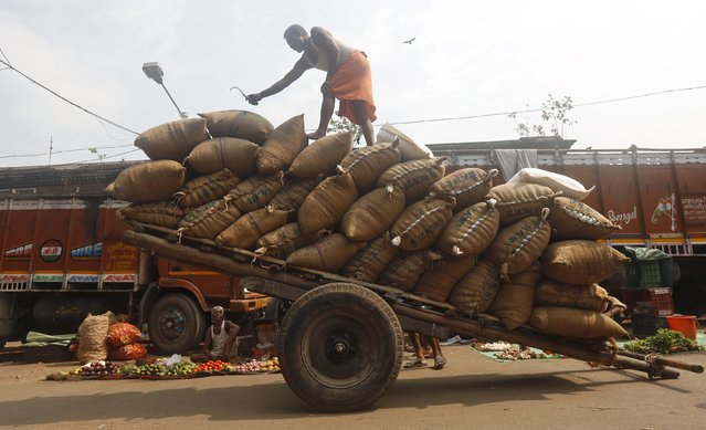 A labourer stacks sacks of flattened rice on a handcart at a wholesale market in Kolkata, India, April 18, 2016. (Photo by Rupak De Chowdhuri/Reuters)