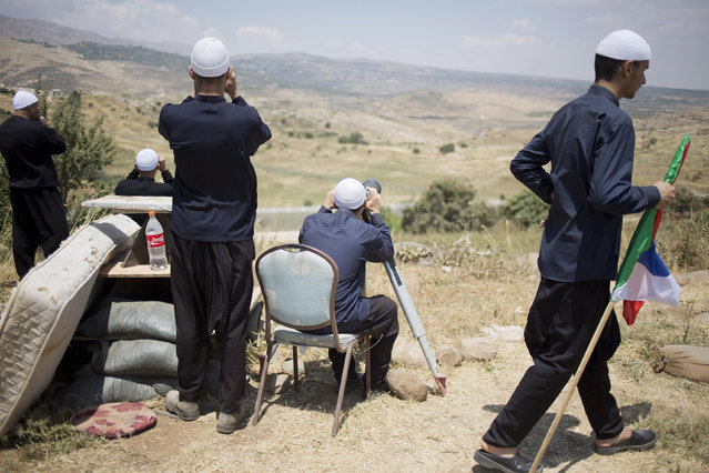 Members of Israel's Druze minority look at the the fighting between forces loyal to Bashar Assad and rebels in the Druze village of Khader in Syria, from the Israeli controlled Golan Heights, Tuesday, June 16, 2015. As many as 20 members of the Druze minority sect were killed last week, the deadliest violence against the Druze since Syria's conflict started in March 2011, sparking fears of a massacre against the sect. (AP Photo/Ariel Schalit)