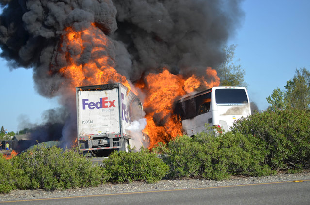 Massive flames engulf a tractor-trailer and a tour bus just after they collide on Interstate 5, Thursday April, 10, 2014, near Orland, Calif. At least 10 people were killed in the crash, authorities said. (Photo by Jeremy Lockett/AP Photo)
