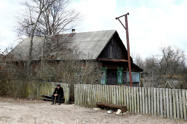 """Ivan Shamyanok, 90, sits in front of his house in the village of Tulgovichi, near the exclusion zone around the Chernobyl nuclear reactor, Belarus April 2, 2016. Shamyanok says the secret to a long life is not leaving your birthplace even when it is a Belarusian village poisoned with radioactive fallout from a nuclear disaster. In April 1986, a botched test at a nuclear plant in Chernobyl, Ukraine, sent clouds of smouldering nuclear material across swathes of Europe and forced more than 100,000 people to leave a permanently contaminated """"exclusion zone"""". April 26, 2016 marks the 30th anniversary of the worst nuclear meltdown in history. (Photo by Vasily Fedosenko/Reuters)"""