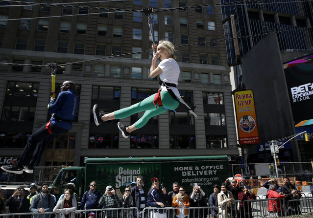 """Former Olympic champions Nastia Liukin, right, and Carl Lewis ride a zip line through Times Square in New York, Wednesday, April 27, 2016. These athletes and many others were participating in an event called """"Team USA's Road to Rio"""" to promote the upcoming Olympic Games. (Photo by Seth Wenig/AP Photo)"""