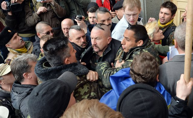 Maidan self-defence activists stop the protesters trying to go inside the Ukrainian paliament in Kiev during a session, on April 15, 2014, as protesters during a rally outside the building demand authorities to take actions against separatism on the eastern part of the country. (Photo by Sergei Supinsky/AFP Photo)