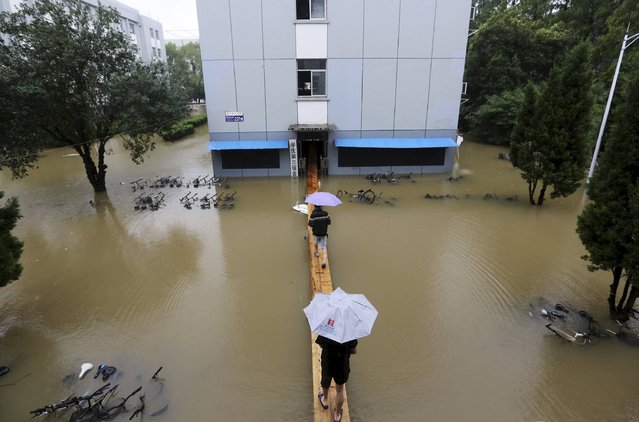 Students walk on a makeshift bridge as they enter their dormitory building which is partially submerged by floodwater, at a university campus after heavy rainfall hit Nanjing, Jiangsu province, China, June 28, 2015. China's top meteorological authority on Sunday continued to warn of heavy rain that have battered parts of the country since last week. (Photo by Reuters/Stringer)