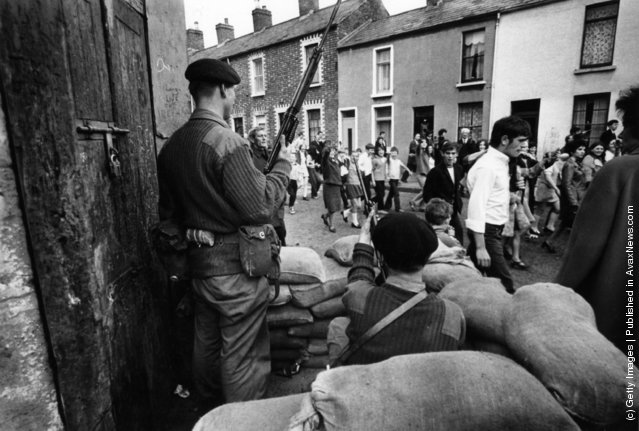 1970:  Marchers on a civil rights demonstration in Belfast pass by an armed British Army sentry point