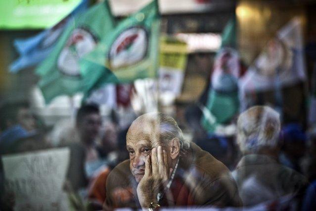 "A man watches the protest ""For April / Against Robberies in Pensions / March of Outrage and Protest"" from a coffee shop in Lisbon, Portugal, 12 April 2014. The protest took place in several cities in Portugal with thousands of pensioners protesting against the austerity measures. (Photo by Mario Cruz/EPA)"
