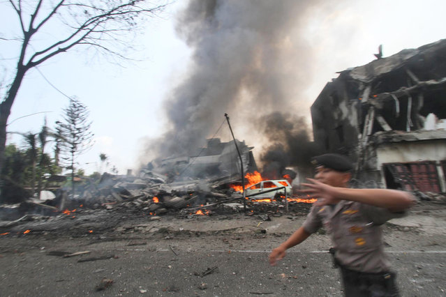A police officer gestures at the crowd near the site where an Air Force cargo plane crashed in Medan, North Sumatra, Indonesia, Tuesday, June 30, 2015. An Indonesian Air Force Hercules C-130 plane with 12 crew aboard has crashed into a residential neighborhood in the country's third-largest city Medan. (Photo by Gilbert Manullang/AP Photo)