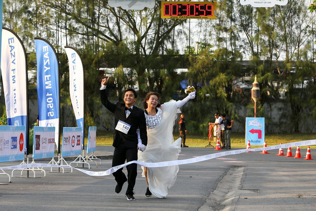 """Rittchai Prasonsin, 27, and Sirada Thamwanna, 29, cross the finish line to win the """"Running of the Brides"""" race in a park in Bangkok, Thailand March 25, 2017. (Photo by Athit Perawongmetha/Reuters)"""