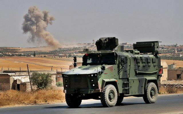 """A Turkish military vehicle is pictured near the town of Maar Hitat in Syria's northern Idlib province on August 20, 2019. Jihadists and allied rebels withdrew from a key area of northwestern Syria today, a monitor said, as President Bashar al-Assad's forces pressed an offensive against the jihadist-run Idlib region. Turkey warned Damascus """"not to play with fire"""" a day after a Syrian regime air strike sought to deter a new Turkish military convoy from entering the area. (Photo by Omar Haj Kadour/AFP Photo)"""