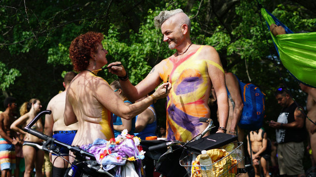 In this photo provided by David Cimetta, Melanie and Jim O'Connor paint each other's nude body while standing next to their bicycles before the start of the Philly Naked Bike Ride in Philadelphia on Saturday August 24, 2019. (Photo by David Cimetta via AP Photo)