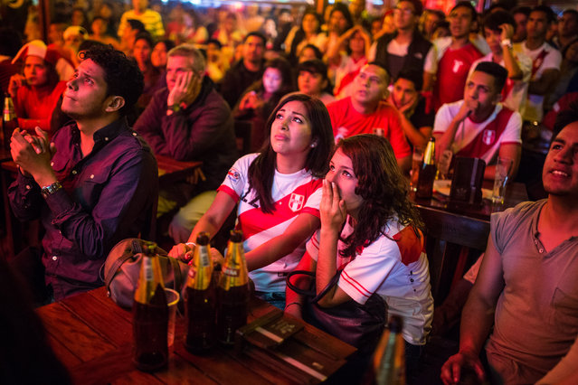 Fans of Peru's national soccer team watch dejectedly on television as their team loses to Chile during a semifinal Copa America match, in Lima, Peru, Monday, June 29, 2015. Chile won the match 2-1. (Photo by Sebastian Castañeda/AP Photo)