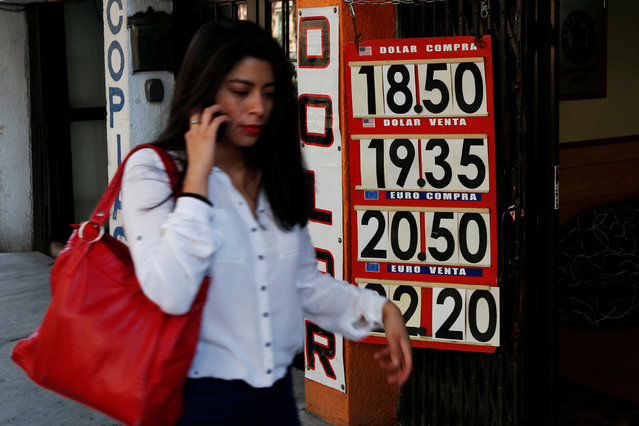 A woman walks in front a board displaying the exchange rate for Mexican peso and U.S. dollar at a foreign exchange house in Mexico City, Mexico March 1, 2017. (Photo by Carlos Jasso/Reuters)