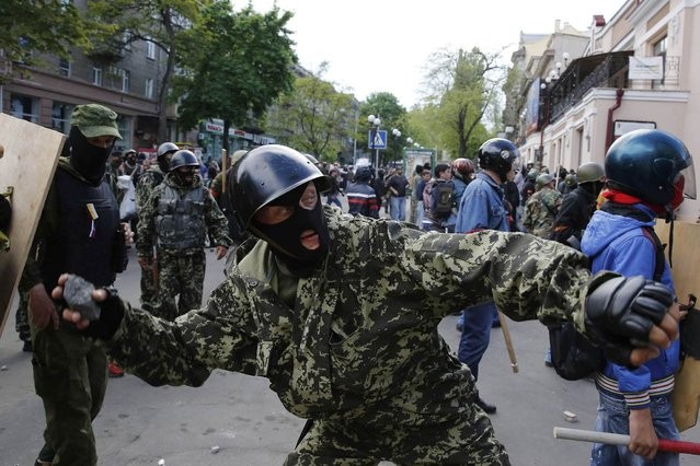 A pro-Russian activist hurls an object at supporters of the Kiev government during clashes in the streets of Odessa May 2, 2014. (Photo by Yevgeny Volokin/Reuters)