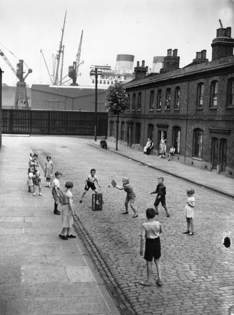 Children playing cricket in a street in Millwall, east London, UK  15th August 1938. A liner on the Thames is in the background. (Photo by Fox Photos/Getty Images)