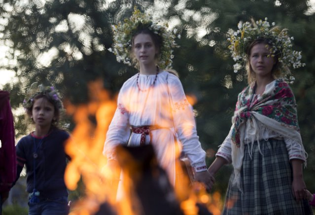 """Belarussian girls walk around camp fire as they take part in the festival of national traditions """"Piatrovski"""" in the village of Shipilovichi, south of Minsk, July 12, 2015. (Photo by Vasily Fedosenko/Reuters)"""