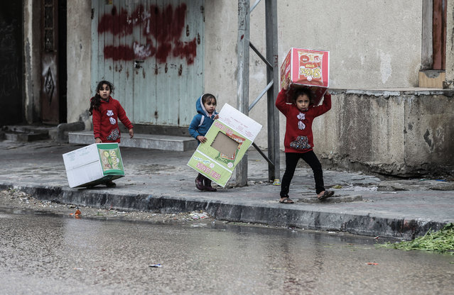 Palestinian girls carry cardboards that will be used to shield them from the rain during a cold front in Rafah, in the southern Gaza Strip, on February 15, 2017. (Photo by Said Khatib/AFP Photo)