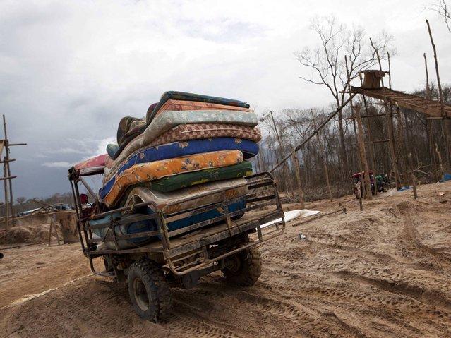 A motortaxi delivers a cargo of mattresses to a mining camp in La Pampa in Peru's Madre de Dios region. (Photo by Rodrigo Abd/AP Photo)