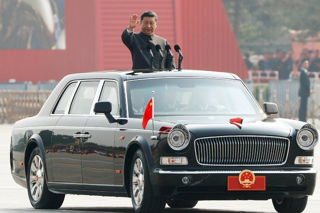 Chinese President Xi Jinping waves from a vehicle as he reviews the troops during the military parade marking the 70th founding anniversary of People's Republic of China, on its National Day in Beijing, China on October 1, 2019. (Photo by Thomas Peter/Reuters)