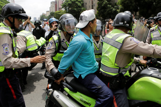 Riot police officers detain a demonstrator on a motorcycle during clashes with opposition supporters in a rally to demand a referendum to remove President Nicolas Maduro in Caracas, Venezuela, May 18, 2016. (Photo by Marco Bello/Reuters)