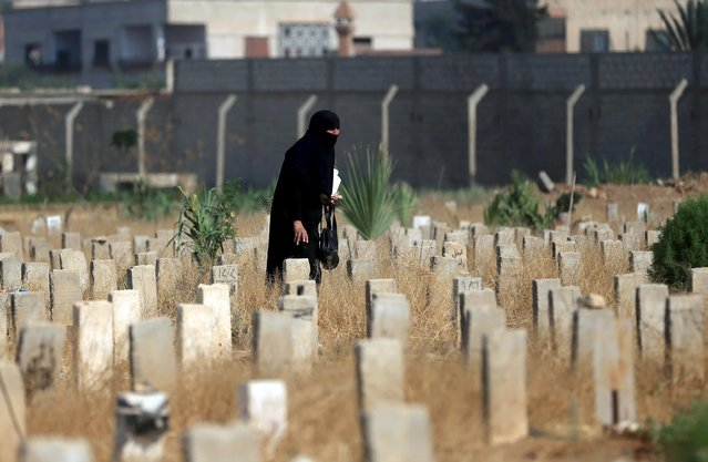 A woman walks past graves as she visits a cemetery, on the first day of the Muslim holiday of Eid al-Fitr, which marks the end of the holy month of Ramadan, in the Douma neighborhood of Damascus, Syria July 17, 2015. (Photo by Bassam Khabieh/Reuters)