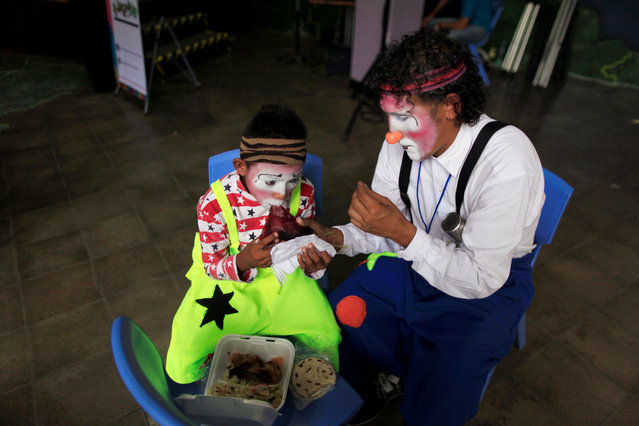 Nariceta and his son Junior (L) eat lunch during the VIII Central America Clown Convention in San Salvador, El Salvador, May 17, 2016. (Photo by Jose Cabezas/Reuters)