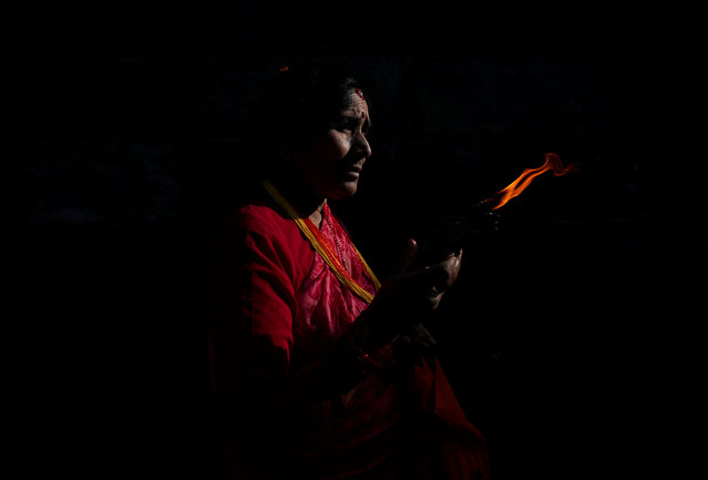 Light illuminates a woman as she offers prayers holding a lamp at the premises of Pashupatinath Temple during the Teej festival in Kathmandu, Nepal on September 2, 2019. The three-day festival, commemorating the union of Goddess Parvati and Lord Shiva, involves sumptuous feasts and rigid fasting. Hindu women pray for marital bliss, the well-being of their spouses and children, and the purification of their own bodies and souls during this period of religious fasting. (Photo by Navesh Chitrakar/Reuters)