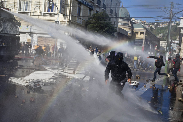 Masked protesters throw stones at a water cannon as police respond with high-pressure blasts of water, near Congress where President Michelle Bachelet was presenting the state-of-the-nation report, in Valparaiso, Chile, Saturday, May 21, 2016. (Photo by Esteban Felix/AP Photo)
