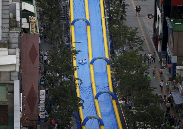 A girl enjoys a ride on a 350-meter (1148 feet) long water slide during 2015 City Silde Festa in central Seoul, South Korea, July 19, 2015. (Photo by Kim Hong-Ji/Reuters)