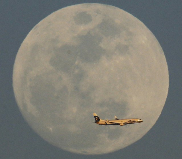 A Alaska Airlines flight passes by the rising moon Sunday, February 21, 2016, in Phoenix. (Photo by Morry Gash/AP Photo)