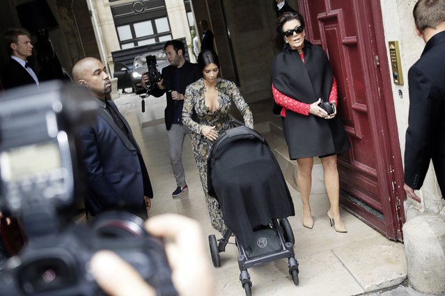 Kim Kardashian pushes a stroller next to Kanye West and her mother, Kris Jenner, right, as they leave their hotel in Paris, on May 23, 2014. (Photo by Kenzo Tribouillard/AFP Photo)