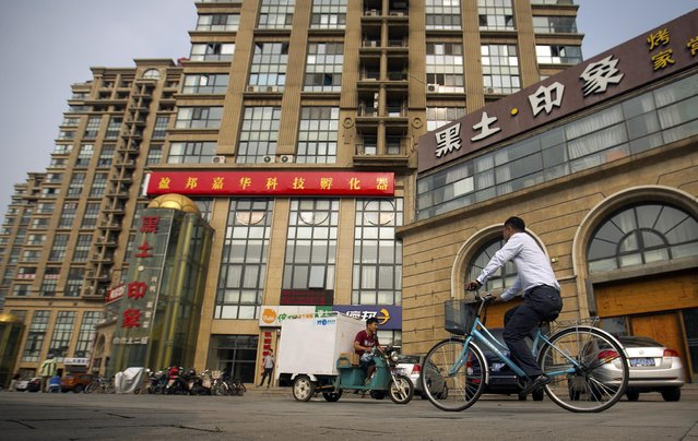 In this Friday, July 17, 2015 photo, a delivery cart and cyclist ride past a building housing the Fengrui law firm in Beijing. Since late May, police across China have detained and called in at least 215 rights lawyers and social activists, including many of Fengrui's lawyers. State propaganda has kicked into high gear to denounce them as rabble-rousers, criminal gangs, and profit-seeking opportunists. (Photo by Mark Schiefelbein/AP Photo)