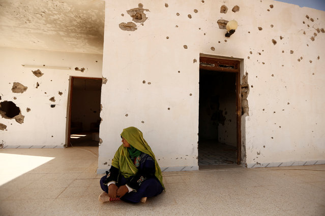 A woman sits outside her house, which was damaged in fighting between Islamic State jihadists and government forces, in Ben Guerdane, near the Libyan border, Tunisia April 12, 2016. (Photo by Zohra Bensemra/Reuters)
