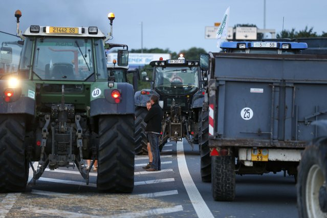 French farmers block the A1 Lille-Paris highway early in the morning in Seclin, northern France, to protest against a squeeze in margins by retailers and food processors, July 22, 2015. (Photo by Pascal Rossignol/Reuters)