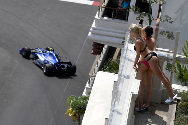 Women look on as Sauber's German driver Pascal Wehrlein steers his car during the second practice session at the Monaco street circuit on May 25, 2017 in Monaco, three days ahead of the Monaco Formula 1 Grand Prix. (Photo by Andrej Isakovic/AFP Photo)