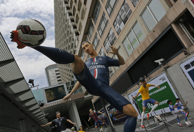 Giant size figures of Swedish striker Zlatan Ibrahimovic, left, and Brazilian striker Neymar, right, are displayed outside a shopping mall in Hong Kong, Thursday, June 12, 2014, to promote the upcoming 2014 World Cup in Brazil. A total of seven 3.5 meters to 4 meters (11 feet 6 inch to 13 feet one inch) tall figures of famous players attract many soccer fans. (Photo by Vincent Yu/AP Photo)