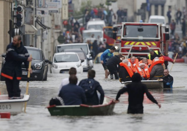French firefighters on small boats evacuate residents from a flooded area after heavy rainfall in Nemours, France, June 1, 2016. (Photo by Christian Hartmann/Reuters)