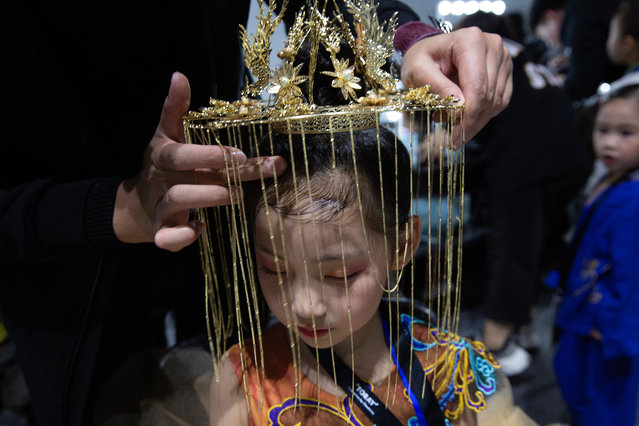Chinese child model Chen Ruoxi has a head dress put on backstage before the brand Van Monfe show during the China Fashion Week Kids Fashion segment in Beijing, China, 01 November 2019. More than 60 children and their parents gathered at the 751 Tank venue for a rehearsal of the runway show for children fashion brand Van Monfe. It is just one of the 35 shows dedicated to kids fashion during the China Fashion Week running from 25 October to 02 November 2019. (Photo by How Hwee Young/EPA/EFE)