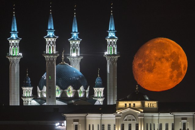The full moon rises over the illuminated Kazan Kremlin with the Qol Sharif mosque illuminated in Kazan, the capital of Tatarstan, located in Russia's Volga River area about 700 km (450 miles) east of Moscow, early Wednesday, July, 29, 2015. (Photo by Denis Tyrin/AP Photo)