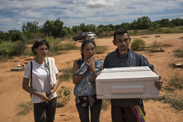 Roberto Parra carries the remains of his son Matias Alejandro alongside his wife Maria Isabel Parra and daughter Alejandra Parra at San Sebastian municipality cemetery before burying him in Maracaibo, Venezuela, November 27, 2019. Parra said his 19-day-old boy died after he was born with lung problems at a public hospital, where, after his wife was turned away from the first hospital, was left to deliver alone in a dirty chair before doctors rushed her up the stairs with her baby's head already exposed. Although the baby was born with respiratory problems, they were told to take him home because he could get sicker if they stayed. (Photo by Rodrigo Abd/AP Photo)