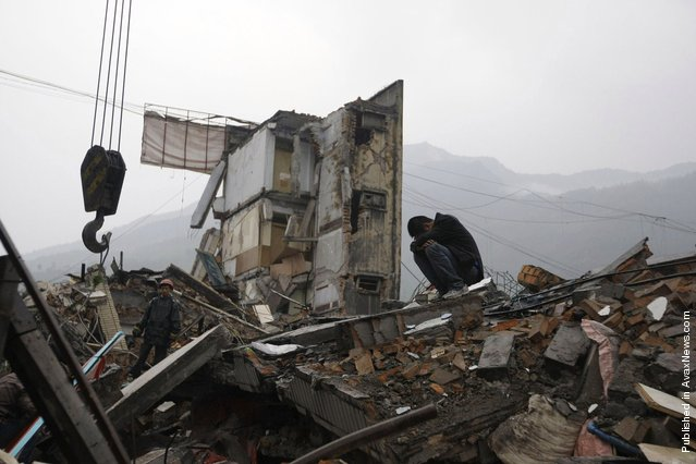 A man cries next to a rescue worker on the roofs of destroyed houses after an earthquake, in Hanwang town in Mianzhu, located around 83 km (50 miles) north of Chengdu, May 13, 2008
