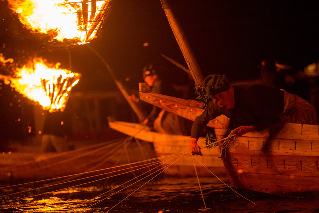 """A cormorant master uses sea cormorants to catch sweetfish on July 2, 2014 in Gifu, Japan. In this traditional fishing art """"ukai"""", a cormorant master called """"usho"""" manages cormorants to capture ayu or sweetfish. The ushos of River Nagara have been the official staff of the Imperial Household Agency of Japan since 1890. Currently six imperial fishermen of Nagara River conduct special fishing to contribute to the Imperial family eight times a year, on top of daily fishing from mid-May to mid-October. (Photo by Chris McGrath/Getty Images)"""