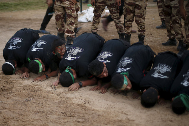 "Young Palestinians form an obstacle to be jumped over during a military-style exercise graduation ceremony organised by the Hamas movement, in Gaza City August 5, 2015. Thousands of young Palestinians joined Hamas military-style summer camps during school vacation in the Gaza Strip to prepare them to ""confront any possible Israeli attack"", organisers said. (Photo by Suhaib Salem/Reuters)"
